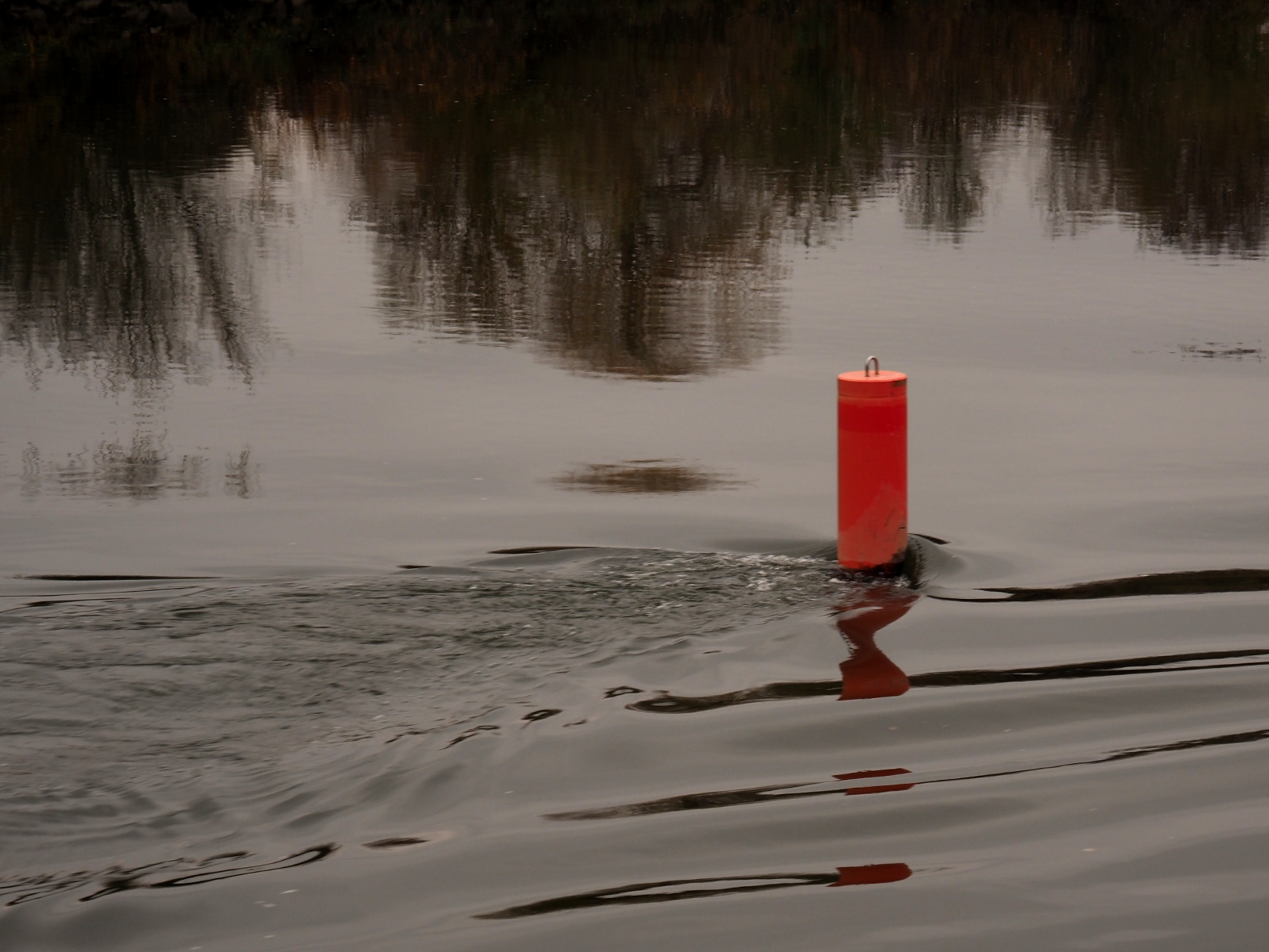 Red mooring post in flowing river